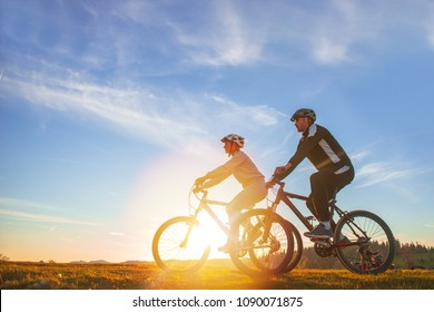 Happy mountainbike couple outdoors have fun together on a summer afternoon sunset