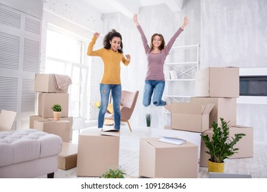Happy to move in. Upbeat young girls jumping happily in the living room of their new apartment before unpacking boxes with their belongings
