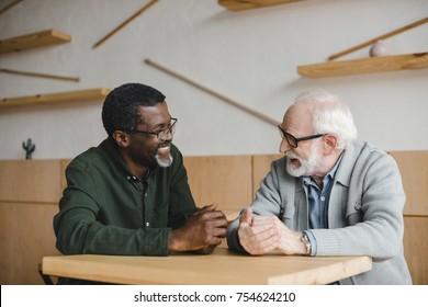 happy muliethnic senior friends having discussion