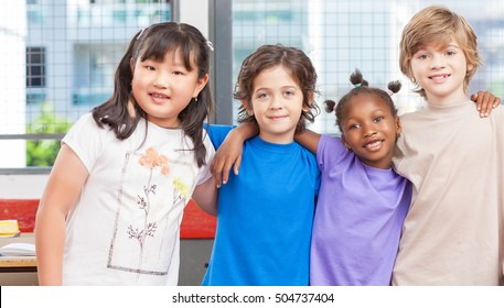 Happy multi ethnic classmates hugging at primary school.