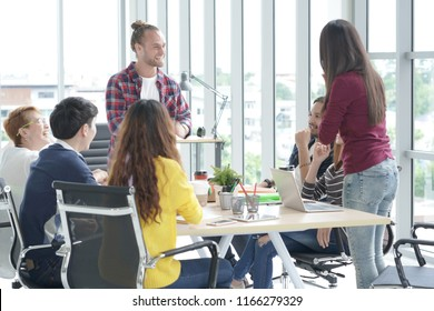Happy Multi Ethnic Creative team in smart casual wear having a meeting while standing