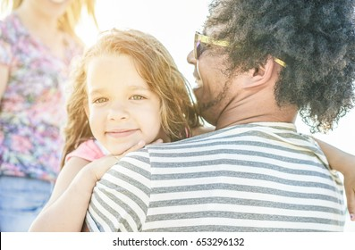 Happy multi ethnic family having fun on the beach - Diverse culture couple playing with daughter on summer vacation - Travel,love,holidays concept - Soft focus on child eye, mouth , nose - Warm filter
