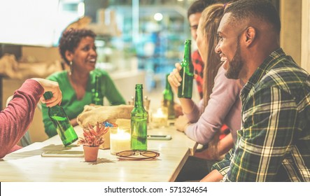 Happy multi ethnic friends toasting bio organic beer in bar pub restaurant - Young people drinking cider and laughing together - Positive mood concept - Focus on right man eye - Warm cinematic filter