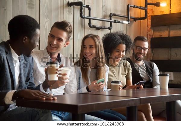 Joyeux groupe multiethnique d'amis parlant avec des smartphones dans un café, des jeunes gens divers riant en s'amusant à une pause café dans un café, de joyeux millénaires appréciant de se rencontrer dans un café