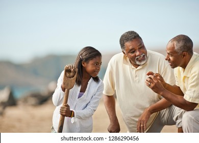 Happy multi generational family talking on a beach.
