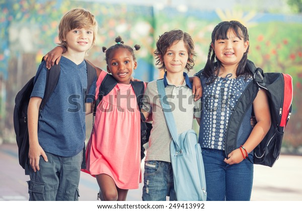 Happy multi race classroom embracing in the schoolyard.