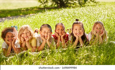 Happy multicultural children lie on a green field in summer as a concept for integration and friendship