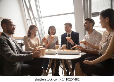 Happy multicultural company staff workers group business team having fun eating pizza together in office, cheerful diverse employees talk laugh share lunch food meal enjoy party at work sit at table