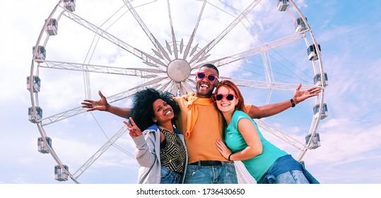 Glückliche multikulturelle Freunde, die Spaß haben am Riesenrad zu stehen - fröhliche, multiethnische SchülerInnen begrüßen eine positive Einstellung und posieren für das Foto - Konzept von Freundschaftsreise und Freude - Image