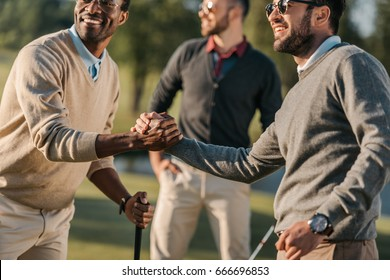 happy multicultural friends shaking hands while playing golf on golf course