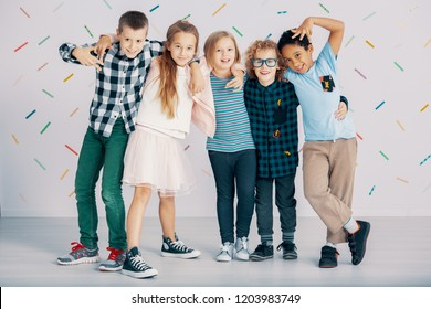 Happy multicultural group of kids have fun against colorful wallpaper