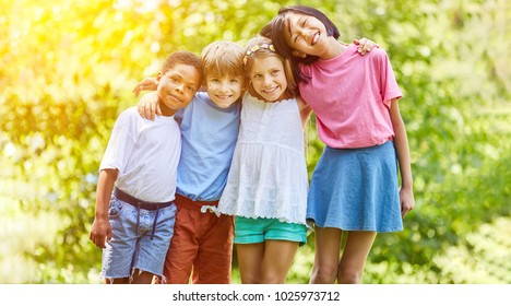 Happy multicultural group of kids hugs each other in summer