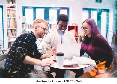Happy multicultural hipster guys browsing dunny web articles during laptop networking in university campus, cheerful male and female millennials searching positive medial files on computer