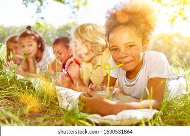Happy multicultural kids drink water with straw in summer on a meadow
