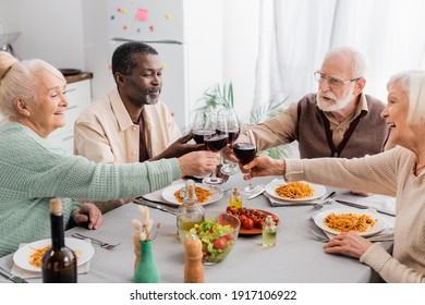 happy multicultural pensioners clinking glasses of red wine during lunch