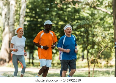 happy multicultural senior men and retired woman running in park
