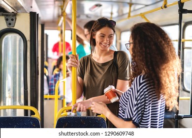Happy multicultural teenage girls chatting and standing in the city bus.