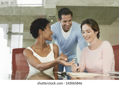 Happy multiethnic business people with notepad planning at conference table