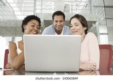 Happy multiethnic business people using laptop at conference table