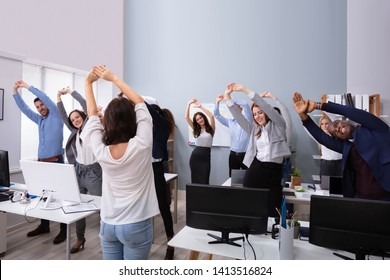 Happy Multi-ethnic Businesspeople Raising Hands Doing Stretching Exercise In Office