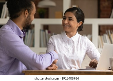 Happy multiethnic businesspeople shake hands close deal make agreement at meeting in office. Smiling African American businessman handshake excited Indian female client, get acquainted at briefing.