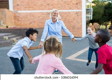 Happy multiethnic children having fun and playing ring around the rosie with teacher.Pupils and cheerful woman holding hands all together and playing at summer camps. School kids outdoor.
