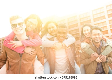 happy multiethnic college students having fun - group of cheerful international students outside university - boys carrying girls on shoulders piggybacking - custom colors and sun burst effects added