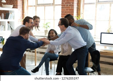 Happy multi-ethnic corporate team employees join hands together at group meeting, office workers celebrating success promising unity help support in teamwork engaged in motivational business training