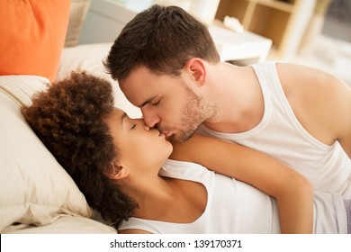 Happy multiethnic couple kissing in bed.