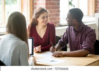 Happy multiethnic couple looking at each other before signing contract in front of female real estate agent. African american man holding pen, preparing to sign the lease for new house or apartment.