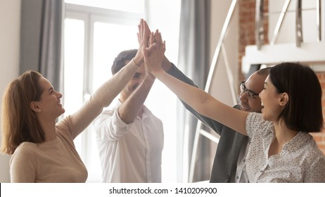 Happy multiethnic employees business team engaged in teamwork teambuilding give high five together involved in celebrating corporate success integrity great professional achievement results in office