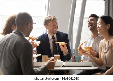 Happy multiethnic employees have fun eating tasty Italian fast food from delivery service, smiling diverse colleagues chat laughing enjoying delicious pizza from takeaway during lunch break in office