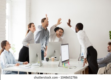 Happy multi-ethnic employees sales team giving high five together celebrating corporate success and good relations, diverse group of office people joining hands excited by common victory achievement