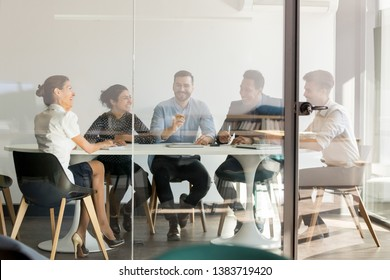 Happy multiethnic employees sit at office desk laugh talking with business client at meeting, smiling business people joke speak negotiating at briefing with female partner in conference room