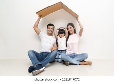 Happy multiethnic family holding roof over their heads as house construction goal concept.