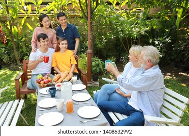 Happy multiethnic family sitting at a breakfast table in backyard outdoor on sunny day with smiling face.