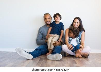 Schöne multiethnische Familie, die mit Kindern auf dem Boden sitzt. Lächelndes Paar sitzt mit zwei Söhnen und Blick auf die Kamera. Mutter und schwarzer Vater mit ihren Kindern, die sich auf die Wand mit Kopienraum.
