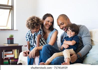 행복한 다민족 가족이 함께 웃으며 소파에 앉아 웃고 있다.집에서 아들들과 노는 밝은 부모들.흑인 아버지는 어머니와 오빠가 웃는 동안 어린 소년을 간지럽혔다.