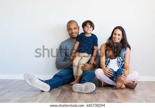 Happy multiethnic family sitting on floor with children. Smiling couple sitting with two sons and looking at camera. Mother and black father with their children leaning on wall with copy space.