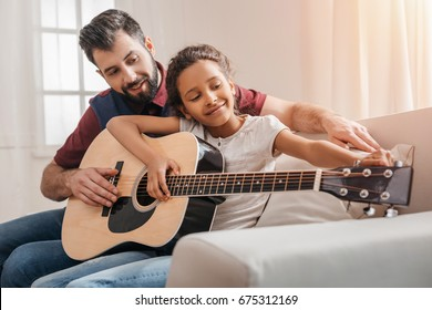 Happy multiethnic father and daughter playing guitar on sofa at home