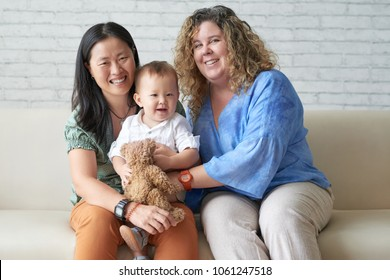 Happy multi-ethnic female couple with their adorable baby boy