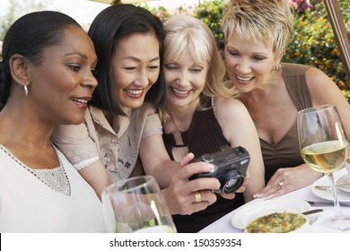 Happy multiethnic female friends looking at photos on digital camera at garden party