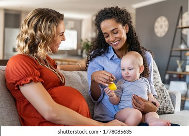 Happy multiethnic friends with child sitting on couch. Pregnant mother relaxing with her girlfriend. Pregnant lesbian gay couple with one toddler son, assisted fertilization and adoption concept.