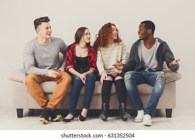 Happy multiethnic friends or collegaues in casual clothes sitting on sofa in living room and talking, leisure time