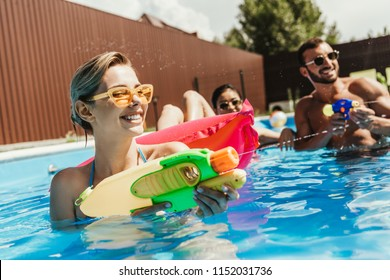 happy multiethnic friends playing with water guns in swimming pool