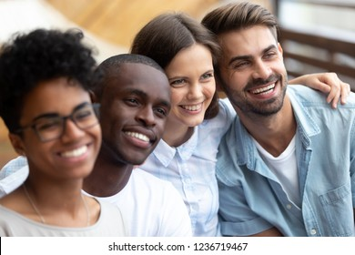 Happy multiethnic friends posing for photo together close up, excited smiling people making picture, colleagues, student in cafe embracing, having fun together, multiracial friendship concept