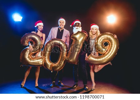 2373d18a99a9d happy multiethnic friends in santa hats holding 2019 new year golden  balloons on black with backlit