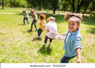 happy multiethnic kids playing tug of war in park
