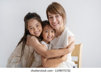 Happy multiethnic little girl hugging sister and mother and smiling at camera. Joyful family of three wearing festive outfits spending time together. Familial affection concept.