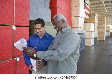 Happy multiethnic men stock taking in warehouse
